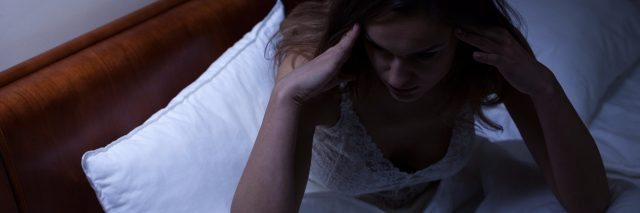 woman in bed having trouble sleeping next to clock reading 3 a.m.