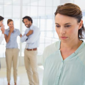 woman looking upset with her coworkers whispering behind her