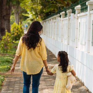 Mother and daughter holding hands, walking down sidewalk
