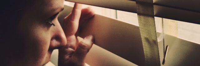 woman peeking through her blinds