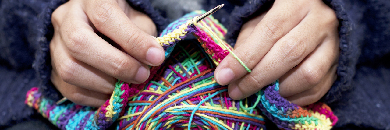 a close up on hands knitting