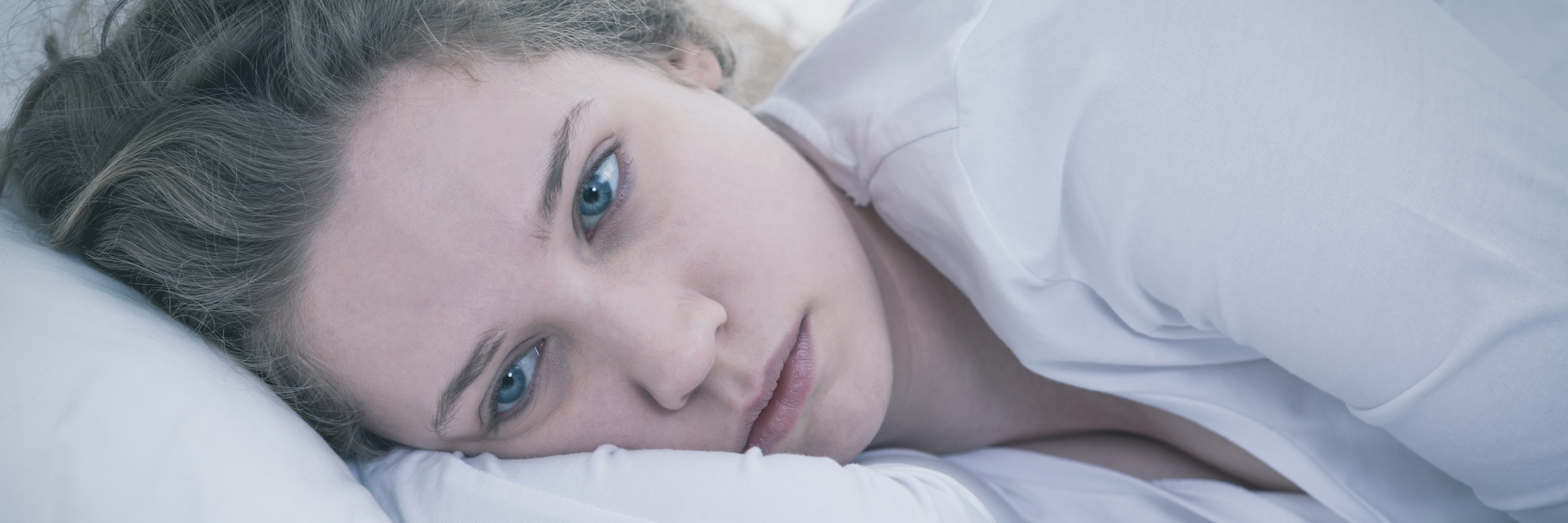 close up of woman lying in bed sad and depressed