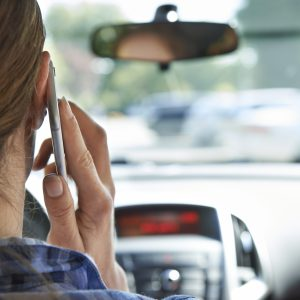 woman talking on phone while in car driving