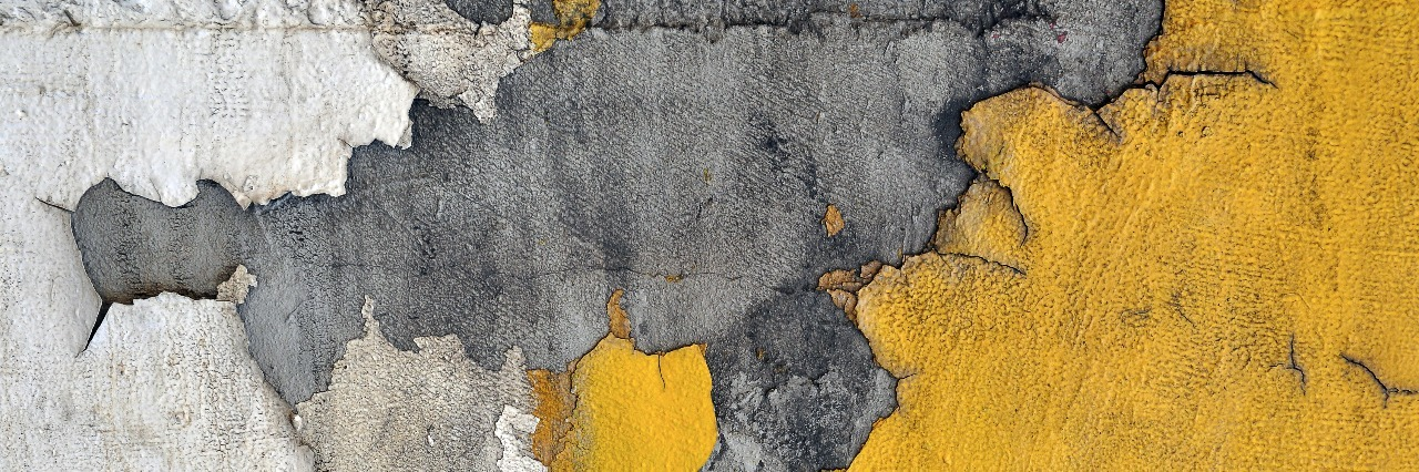 yellow paint chipping away from urban wall