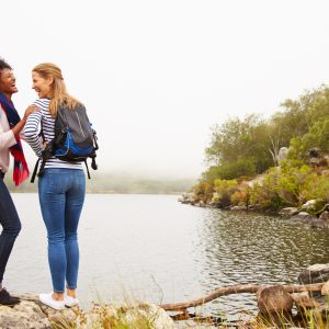 two female friends hiking near a lake and laughing