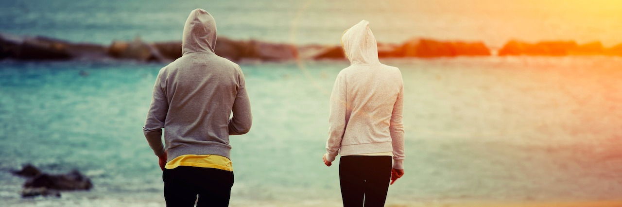 A woman and a man waring long sleeves at the beach