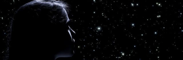 A woman looks in the dark, towards the stars.