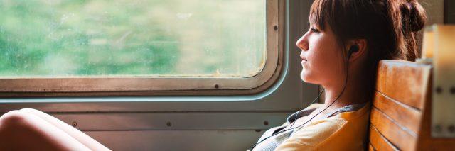 sad or contemplative girl on train listening to music on headphones