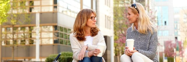 two women sitting outside and talking