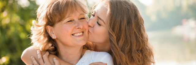 teenage girl hugging and kissing her mom on the cheek