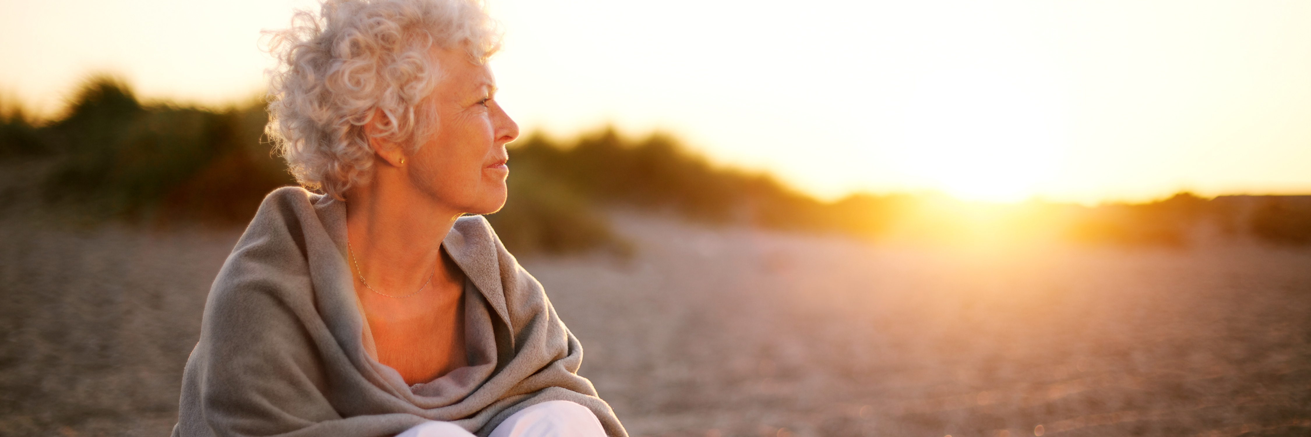 senior woman sitting on beach looking at horizon