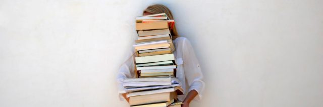 A woman holding a stack of books