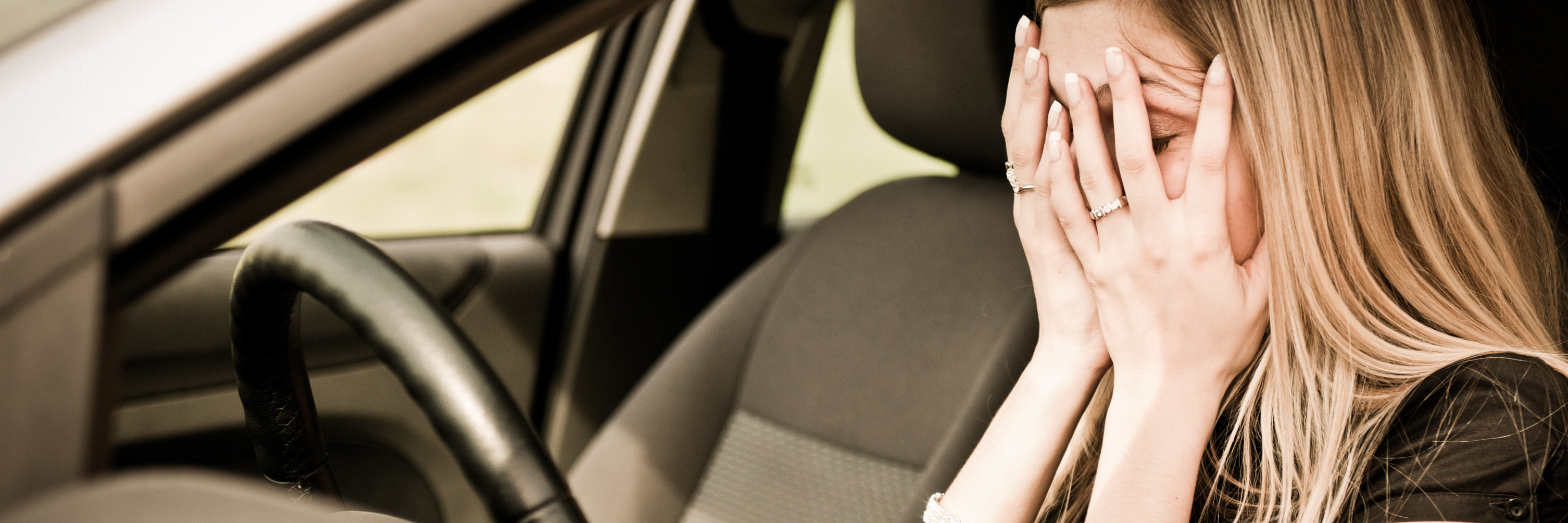 young anxious woman sitting in car with hands over eyes