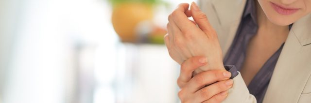 woman sitting at a desk and holding her wrist in pain