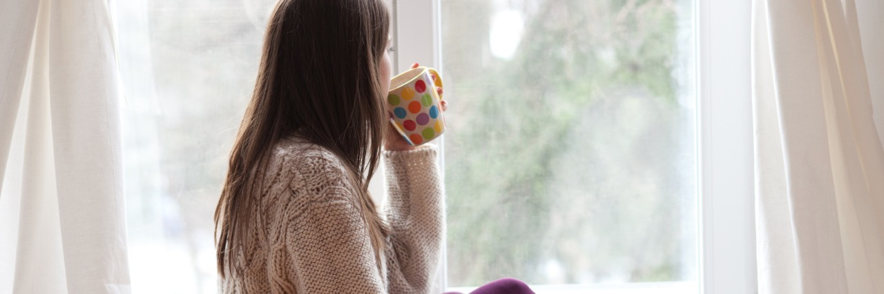 woman drinking tea and looking out the window