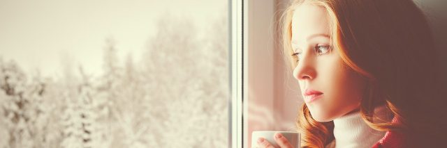 A woman drinking a cup of tea and staring out a window