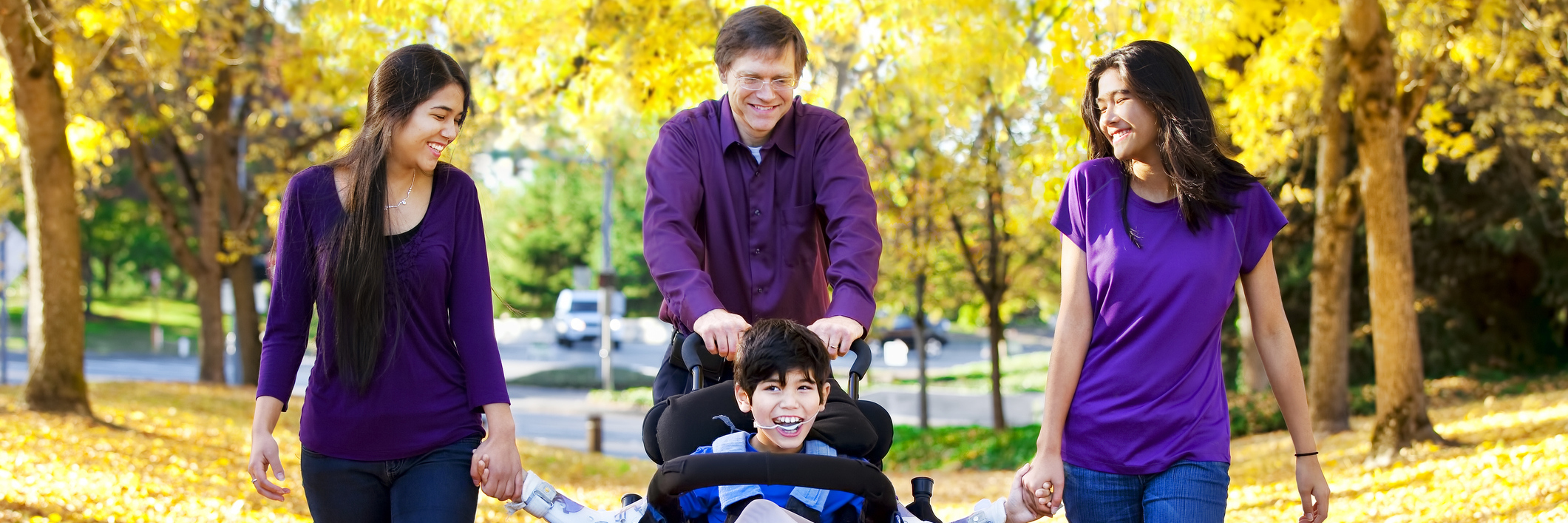 Family with disabled child in wheelchair walking among autumn leaves.