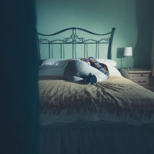 woman lying on bed alone in dark room