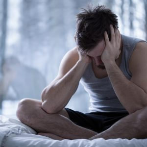 man with depression with head in hands sitting cross legged on bed