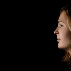 profile of young pensive woman with red hairs on black background