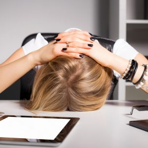 Woman with her head on her desk.