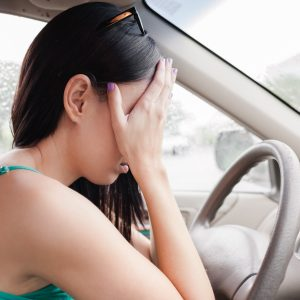 tired stressed upset woman driver with hands covering eyes