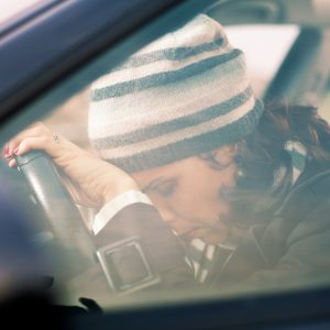 woman sitting in a car and leaning her head on the steering wheel