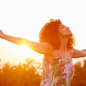woman standing outside with her arms outstretched and the sun setting behind her