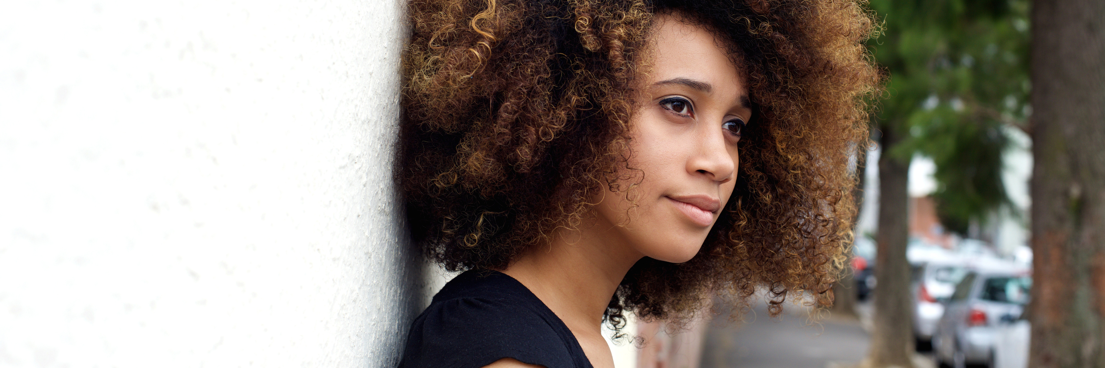 Side portrait of young african american woman leaning against wall and looking away