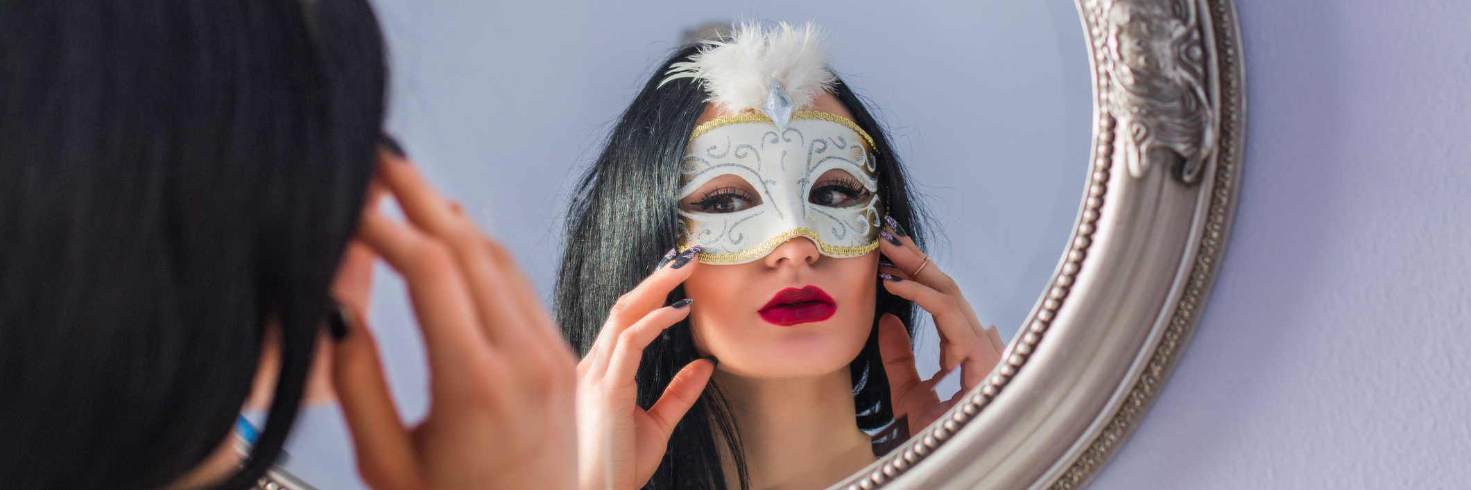 Woman looks in mirror, taking off mask.