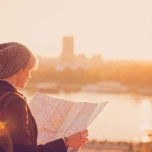 A woman holding a map standing in front of a city
