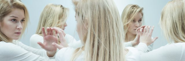 young upset blonde woman surrounded by mirrors looking at reflection
