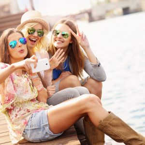 three friends taking a selfie on a pier