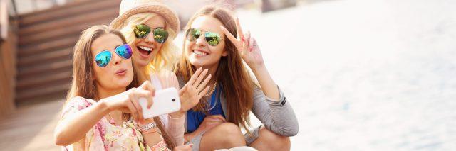 three friends taking a selfie on a pier