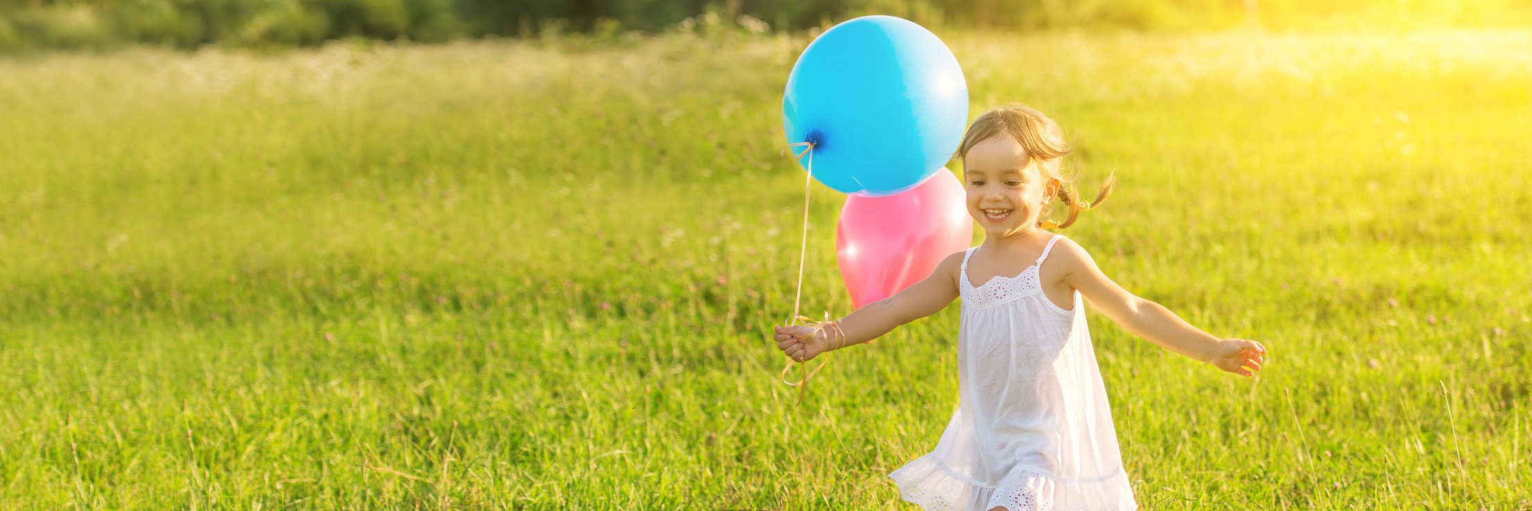 young girl laughing and running through a field with balloons