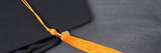 graduation cap with gold tassel on blackboard background