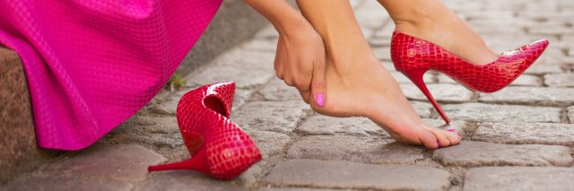 woman sitting on sidewalk wearing green skirt and red shoes, holding foot in pain
