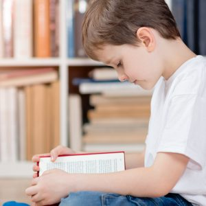 Child with book in the library, sitting on the floor reading