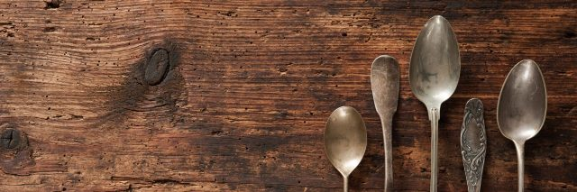 Vintage metal spoons on wooden table