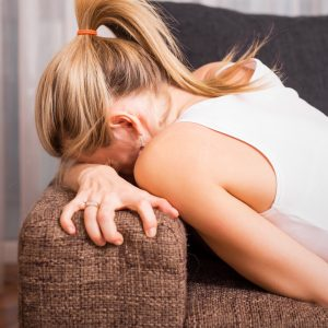 A woman in pain tightly grips the couch, her face buried within it.