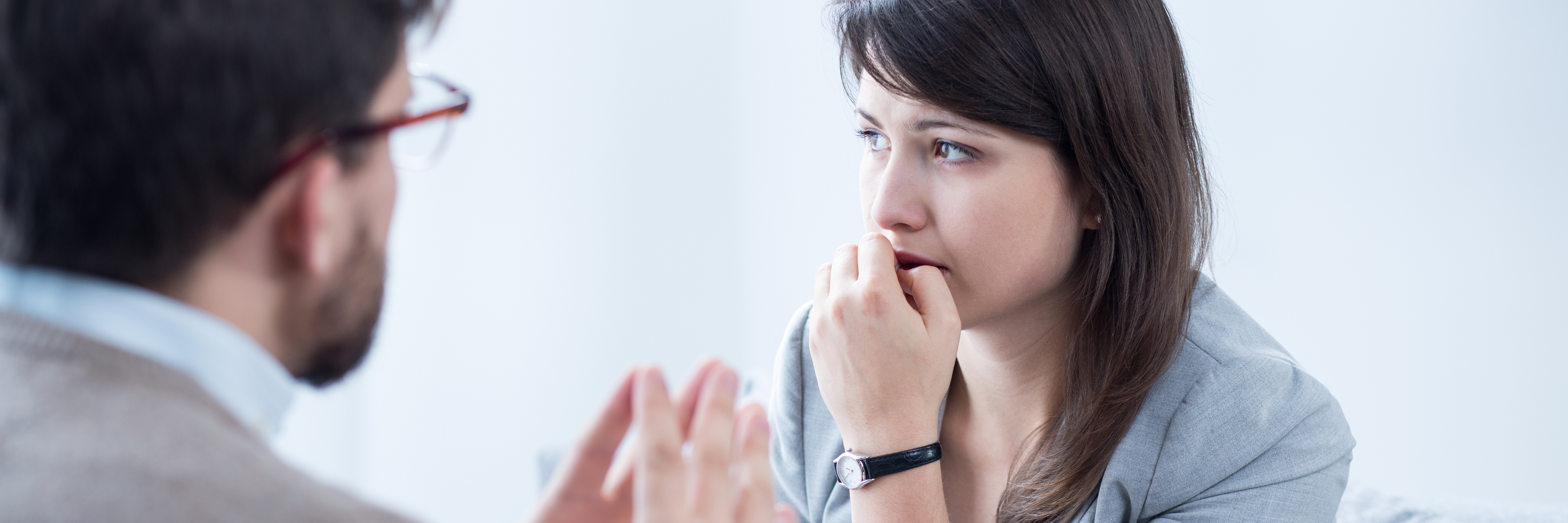 woman biting her nails during appointment with doctor or therapist