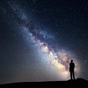 Silhouette of man standing in front of star-filled and Milky Way night sky landscape