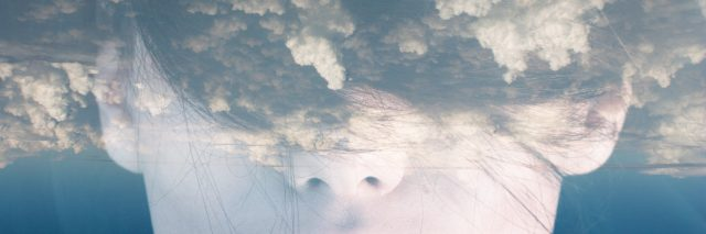 woman's face with double exposure of clouds covering her eyes