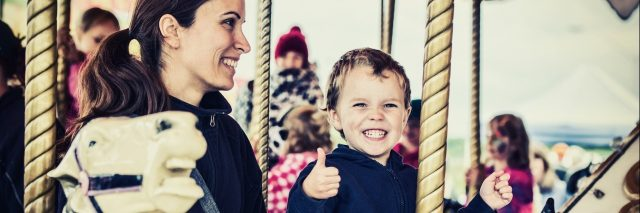 mother and son riding on a carousel