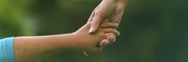 Mom and child holding hands.