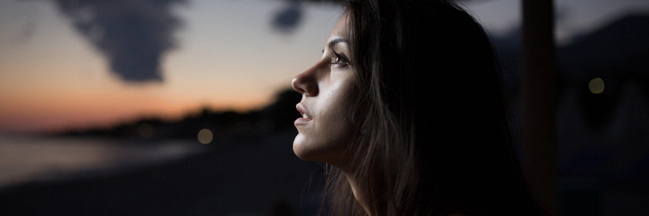 Woman looking out towards the sunset.