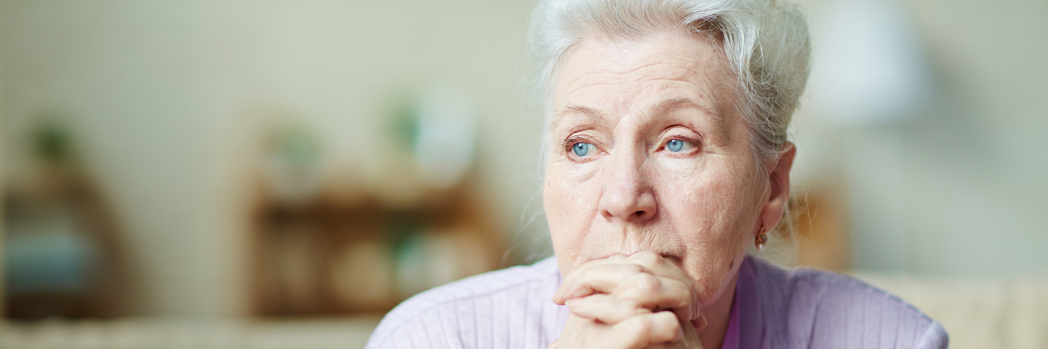 An older woman sits, looking unhappy.