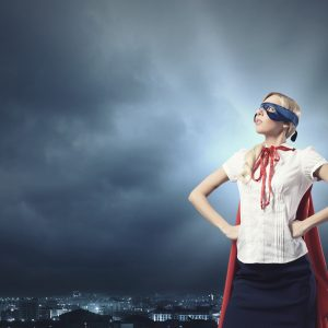 Young woman with superhero outfit outside, looking to the sky.