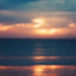 Blurred Image of ocean with sunset and gray clouds