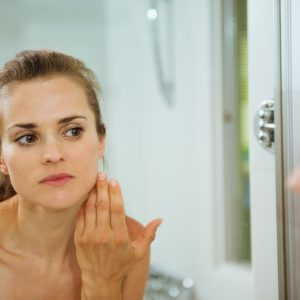 young woman checking her face in bathroom mirror